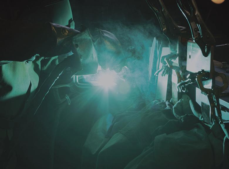 Worker welding a piece of metal.